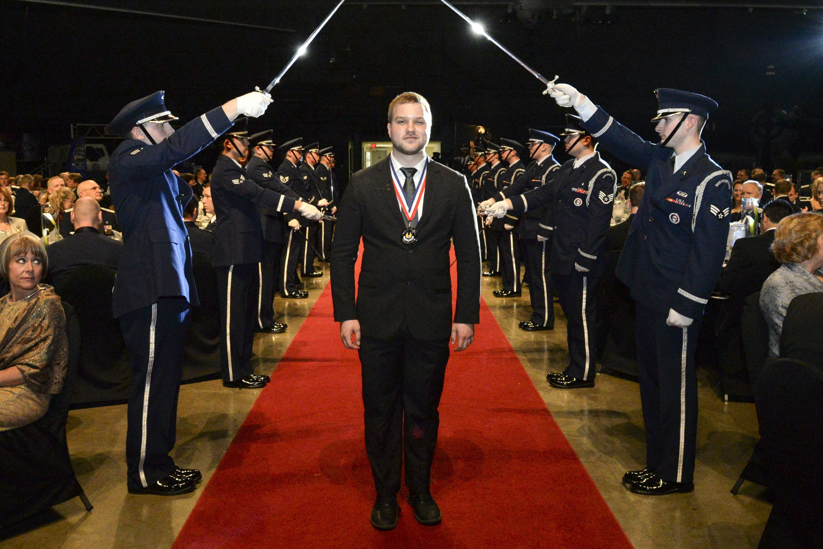 Ty Mick, wearing a medal featuring the AFMC logo, walking on a red carpet between Airmen holding swords at the 2014 AFMC Annual Excellents Awards.